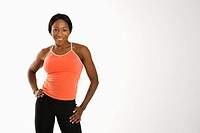 African American young adult woman in athletic wear smiling at viewer with hands on hips