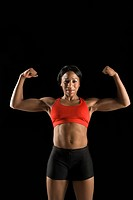 Muscular African American woman wearing athletic apparel with biceps flexed