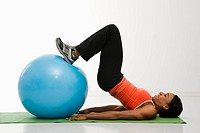 Profile of African American woman stretching on mat with feet on exercise ball