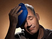 Man holding ice pack on head
