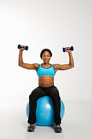 African American young adult woman sitting on exercise ball and raising dumbbells over head