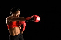 African American young adult woman wearing boxing gloves throwing punch