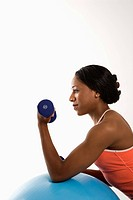 Profile of African American young adult woman leaning on exercise ball holding dumbbell