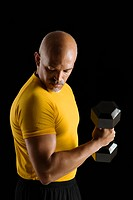 Mid adult multiethnic man wearing yellow exercise shirt doing arm curls while looking at bicep