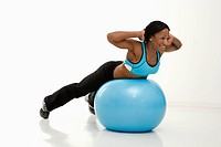 African American young adult woman working out with exercise ball