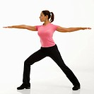 Side view of mid adult multiethnic woman wearing exercise clothing standing in yoga warrior pose.
