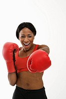 African American young adult woman wearing boxing goves throwing playful punch at viewer