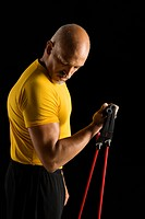 Mid adult multiethnic man wearing yellow exercise shirt exercising with stretch band and looking at bicep