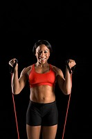 African American young adult woman exercising with resistance tube and smiling at viewer