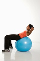 Side view of African American woman balancing on exercise ball doing crunches.
