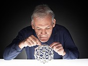 Mature man playing with puzzle