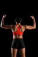 Back view of muscular African American woman with biceps flexed