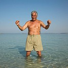Happy senior man on beach with arms raised
