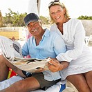 senior couple on beach reading newspaper