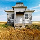Facade of weathered abandoned building with peeling paint in grasslands