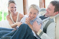 Family smiling and sitting on couch, parents tickling son, portrait for son
