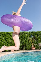 Girl in an inner tube jumping into swimming pool