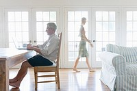 Senior couple in living room, man using laptop at table and woman walking, blurred motion