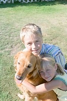 Portrait of girl and boy with Golden Retriever, girl embracing dog (thumbnail)