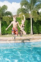 Girl and boy jumping into swimming pool
