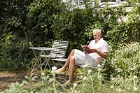 Senior caucasian man reading a book in the garden, Side View
