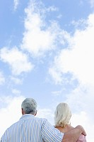 Senior couple under the sky, man putting arm around woman's shoulder, copy space