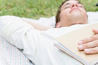 College Boy Lying on Grass with Holding Book (thumbnail)