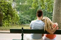 Couple sitting on bench, man putting arm around woman's shoulders, rear view, differential focus