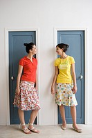 Two caucasian women standing by the doors, Front View, Side View