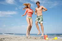 Young couple jumping on sandcastle