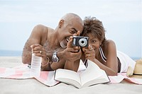 Mature couple looking at digital camera on beach (thumbnail)