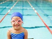 Girl wearing swimming goggles by pool portrait (thumbnail)