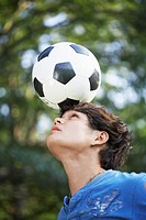 Teenage boy balancing soccer ball on forehead (thumbnail)