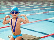 Boy celebrating medal by swimming pool portrait
