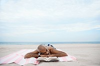 Man sleeping by book on beach