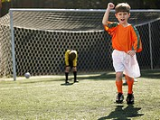 Boy in soccer uniform celebrating, defeated goalkeeper in background portrait