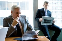 Businessman Reading Financial report, Focus on Foreground