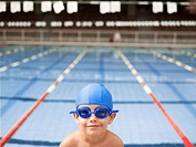 Boy wearing goggles by swimming pool portrait