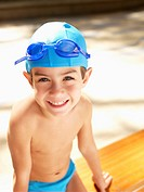 Boy wearing swimming cap and goggles portrait, high angle view