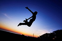 Parcours: A boy practicing jumps to the dusk in the beach