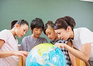 Elementary students and teacher looking at terrestrial globe