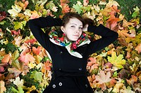 Elevated view of young woman lying on autumn leaves, portrait En stämningsfylld höstbild på en tjej liggandes i en stor färggrann lövhög.