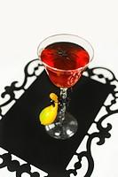Close_up spider in wine glass, studio shot Ett glas innehållande en röd dryck med en spindel i