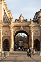 Entrance of building Människor går på Riksgatan med riksdagshusets valv i solljus där man ser skulpturer och tre kronor symbolen på byggnaden.