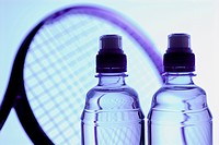 Close_up of two water bottles and a tennis racket