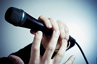 Close_up of a person´s hand holding a microphone