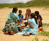 Indian Girls selling trinkets to a tourist on Calungute Beach, Goa, India