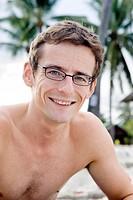 Porträtt av leende man med bar överkropp och glasögon på stranden, närbild. Close_Up Of Mid Adult Shirtless Man With Glasses Sitting On Beach, Smiling...