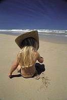 Rear view of girl sitting on sand by sea Flicka med halmhatt leker i sanden på en strand med blått hav