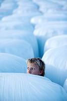 Pojke Bland Inplastade Höbalar Foto: Urban Jörén Kod 926 Copyright Pressens Bild , Close_Up Of Boy 6_7 Hidding In Stack Of Covered Hay Bales